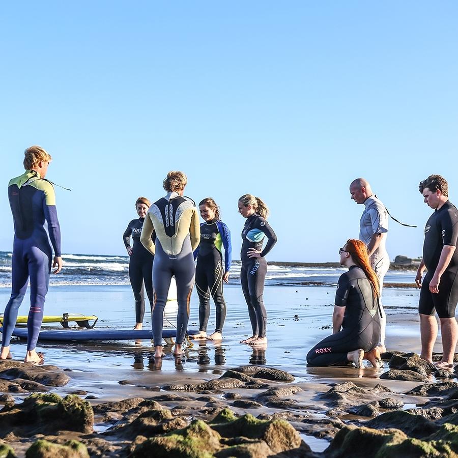 Surfaři v oblečení soul na pobřeží